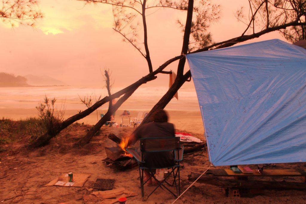 persoon zit op eein eiland bij een vuurtje onder een opgespannen afdekkleed te genieten van het uitzicht over zee